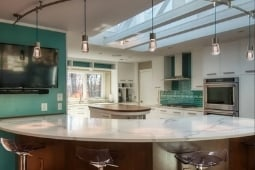 Kitchen Remodeling Services Track Lights with Colored Backsplash and Marble Countertop | Denny + Gardner Design-Build Remodelers