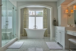 Bathroom Remodeling Services Luxury Bathroom with Freestanding Tub and Walk In Glass Shower with Large Window and Custom Cabinetry for Vanity Area | Denny + Gardner Design-Build Remodelers