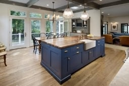 Kitchen Remodeling Services Large Eat-In Island Blue Cabinetry and Exposed Beams with Farmhouse Sink | Denny + Gardner Design-Build Remodelers