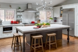 Kitchen Remodeling Services Large Eat-In Island with Modern Light Fixtures and Built-In Appliances | Denny + Gardner Design-Build Remodelers