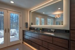 Bathroom Remodeling Services Modern Bathroom Design with Backlit Vanity Mirror and Custom Cabinetry  | Denny + Gardner Design-Build Remodelers